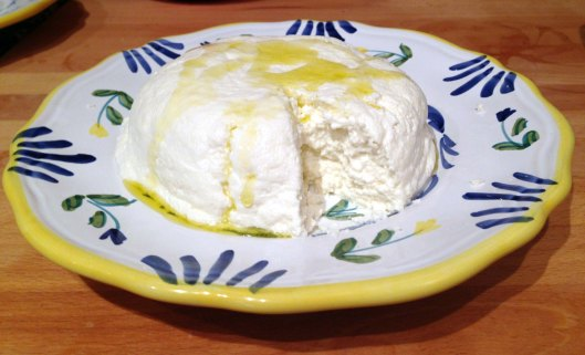 Freshly made ricotta drizzled with olive oil, ready to spread onto bread