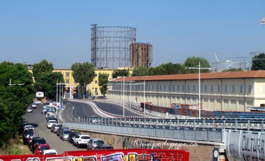 The view on exiting Garbatella Metro Stop.  Via Ostiense is in front, where the yellow building is.  Il Gasometro is behind it.  Centrale Montemartini is just to the left.