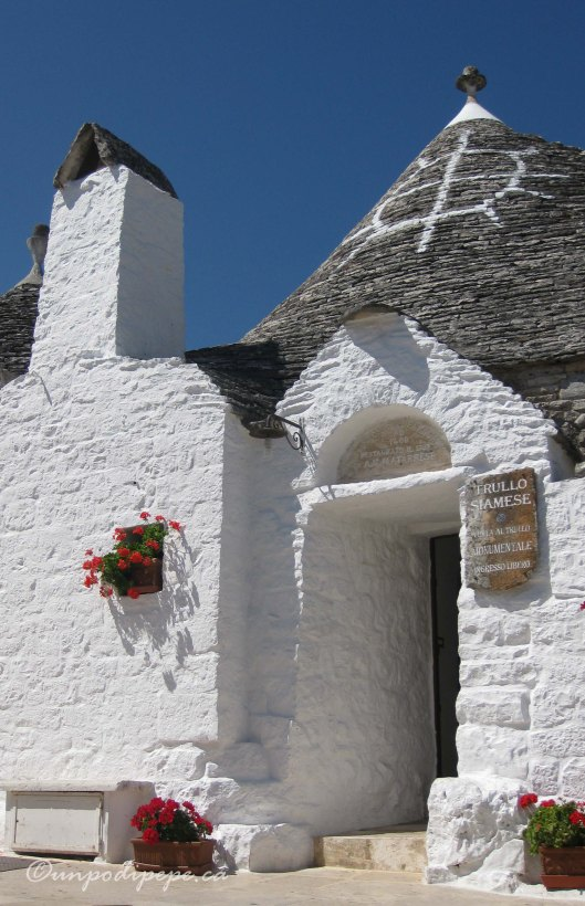 Trullo Siamese.  2 brothers in love with the same woman lived here.  They split it in half and the single brother installed a door into the lane.