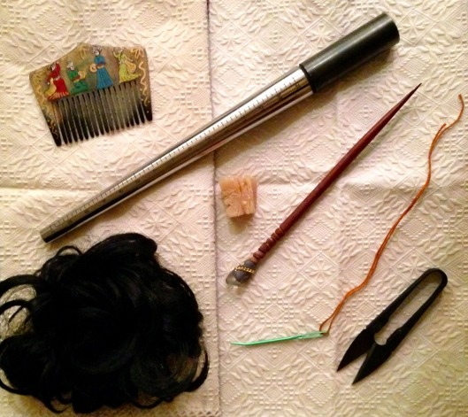 My similated 'Ornatrice Toolbox' containing blunt needle and wool thread. hair piece and hair bodkin, leaf spring scissors, camel bone comb, beeswax and a 'calamistrum' which is actually my ring mandrel, but it is the right shape!