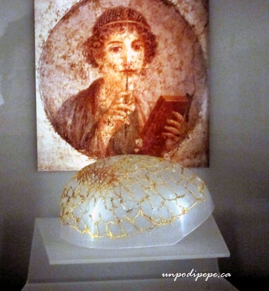 Reticula (hairnet) of finely woven gold, found on Via Tiburtina, Palazzo Massimo. In behind is the poet Sappho wearing a hairnet, from a Pompeiian fresco.