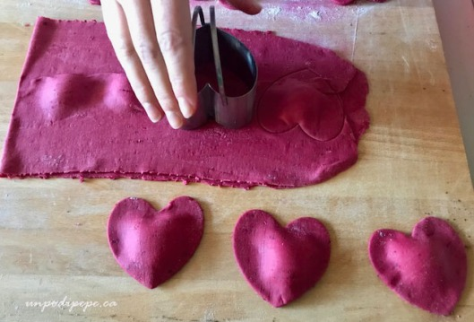 Cutting out heart shaped beet ravioli